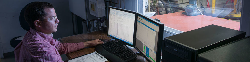 Rotoflow engineer sitting in front of a laptop computer screen to view the results of a spin test on a turboexpander